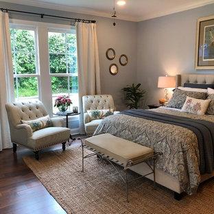 Diseño de dormitorio principal, tradicional renovado, grande, con paredes azules, suelo de madera oscura, chimenea lineal, marco de chimenea de ladrillo y suelo marrón