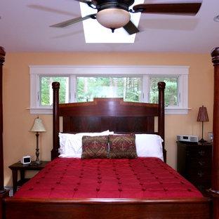 Modelo de dormitorio principal, tradicional renovado, de tamaño medio, con paredes amarillas y suelo de madera en tonos medios