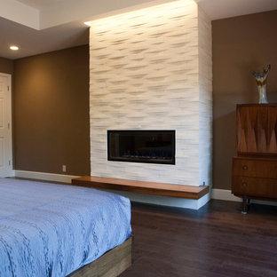 На фото: большая хозяйская спальня в стиле модернизм с коричневыми стенами, темным паркетным полом, стандартным камином и фасадом камина из плитки с