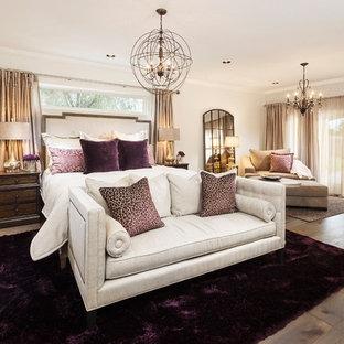 Modelo de dormitorio principal, clásico renovado, grande, con paredes blancas, suelo de madera en tonos medios, chimenea tradicional y marco de chimenea de piedra