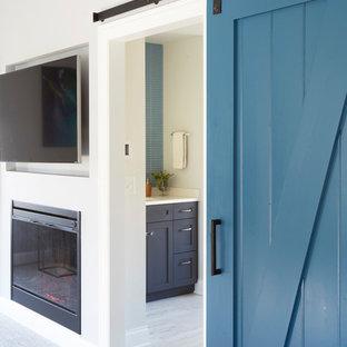 Diseño de dormitorio principal, actual, grande, con paredes grises, moqueta, chimenea tradicional, marco de chimenea de yeso y suelo gris