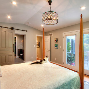 Example of a large transitional master medium tone wood floor bedroom design in St Louis with gray walls and no fireplace