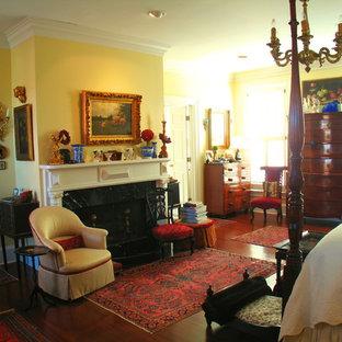 Ejemplo de dormitorio principal, tradicional, grande, con paredes amarillas, suelo de madera en tonos medios, chimenea tradicional y marco de chimenea de piedra