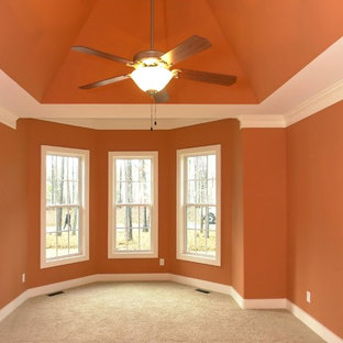 Inspiration for a large transitional master carpeted bedroom remodel in Raleigh with orange walls