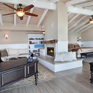 Foto de dormitorio costero con paredes beige, suelo de madera en tonos medios y chimenea de doble cara