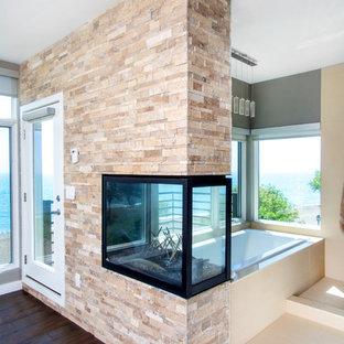 Diseño de dormitorio principal, urbano, de tamaño medio, con paredes grises, suelo de madera oscura, chimenea de doble cara, marco de chimenea de piedra y suelo marrón