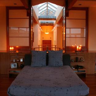 Cette image montre une grande chambre parentale asiatique avec un mur beige, un sol en bois brun, une cheminée standard et un manteau de cheminée en plâtre.