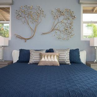 Imagen de dormitorio tropical con paredes azules y suelo de madera oscura
