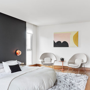 This is an example of a contemporary bedroom in Los Angeles with black walls, light hardwood flooring and no fireplace.