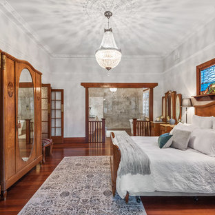 Photo of a large traditional master bedroom in Perth with grey walls, dark hardwood floors, brown floor and no fireplace.