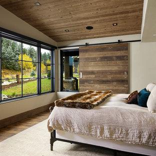 Modelo de dormitorio principal, rústico, de tamaño medio, con paredes blancas, suelo de madera en tonos medios y suelo marrón
