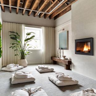 На фото: с высоким бюджетом гостевые спальни среднего размера в современном стиле с белыми стенами, ковровым покрытием, подвесным камином, фасадом камина из штукатурки и синим полом