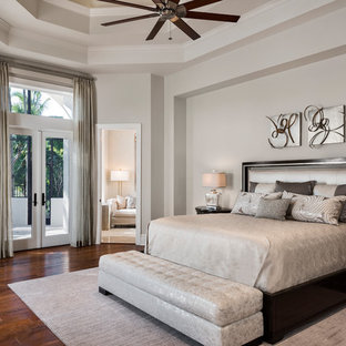 Photo of a transitional master bedroom in Miami with dark hardwood floors, brown floor and white walls.