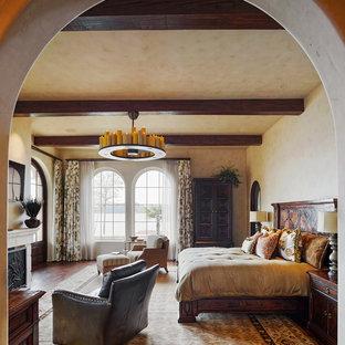 Immagine di una camera da letto mediterranea con pareti beige, parquet scuro e camino classico