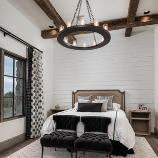 This is an example of a mediterranean bedroom in Phoenix with white walls, medium hardwood floors and brown floor.