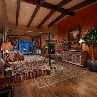 Esempio di una camera da letto mediterranea con pareti arancioni, pavimento in legno massello medio e camino ad angolo