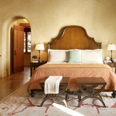 Tuscan medium tone wood floor bedroom photo in San Francisco with beige walls