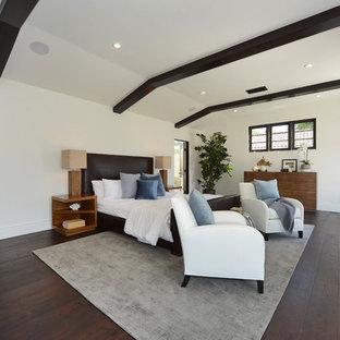 ロサンゼルスの大きい地中海スタイルのおしゃれな主寝室 (白い壁、濃色無垢フローリング、両方向型暖炉、漆喰の暖炉まわり、茶色い床) のインテリア
