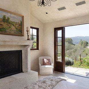 Inspiration för ett mellanstort medelhavsstil gästrum, med en standard öppen spis, beige väggar, kalkstensgolv och en spiselkrans i sten