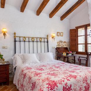 На фото: хозяйская спальня среднего размера в средиземноморском стиле с белыми стенами и полом из терракотовой плитки без камина с
