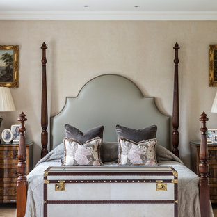 This is an example of a victorian master bedroom in London with beige walls.