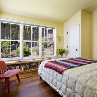 Imagen de dormitorio rural con paredes amarillas y suelo de madera en tonos medios