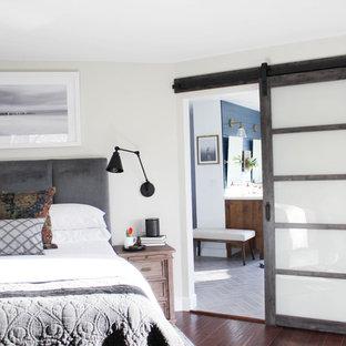 Immagine di una camera matrimoniale minimalista di medie dimensioni con pareti grigie, parquet scuro, camino sospeso, cornice del camino in legno e pavimento marrone