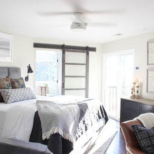 Diseño de dormitorio principal, minimalista, de tamaño medio, con paredes grises, suelo de madera oscura, chimeneas suspendidas, marco de chimenea de madera y suelo marrón