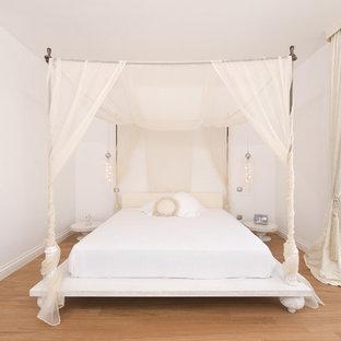 Eklektisches Schlafzimmer ohne Kamin mit weißer Wandfarbe und hellem Holzboden in Sonstige