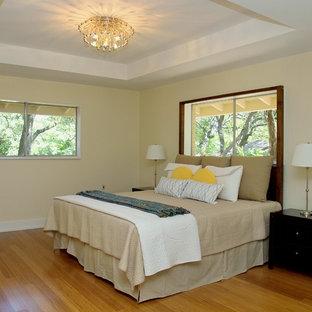 Ejemplo de dormitorio ecléctico, de tamaño medio, con paredes amarillas y suelo de bambú