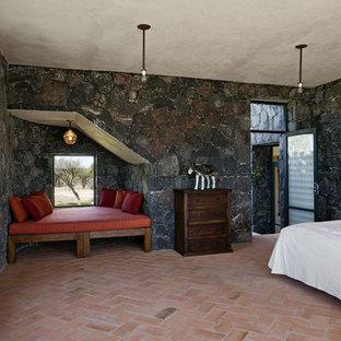 Cette image montre une chambre méditerranéenne avec un sol en brique et un mur gris.