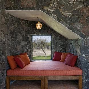 Стильный дизайн: спальня в средиземноморском стиле с кирпичным полом и серыми стенами - последний тренд