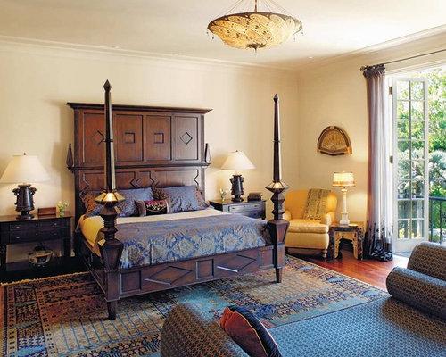 Example Of A Tuscan Medium Tone Wood Floor Bedroom Design In Los Angeles  With Beige Walls