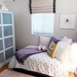 Immagine di una piccola camera da letto moderna con pareti rosa, pavimento in legno massello medio, nessun camino e pavimento marrone