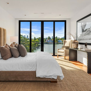Inspiration for a modern medium tone wood floor and brown floor bedroom remodel in Los Angeles with white walls