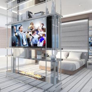 Modelo de dormitorio principal, minimalista, extra grande, con paredes beige, suelo de mármol, chimenea de doble cara, marco de chimenea de metal y suelo blanco