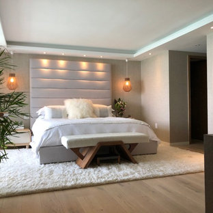 Modelo de dormitorio principal, minimalista, de tamaño medio, con paredes beige, suelo de madera clara y suelo blanco