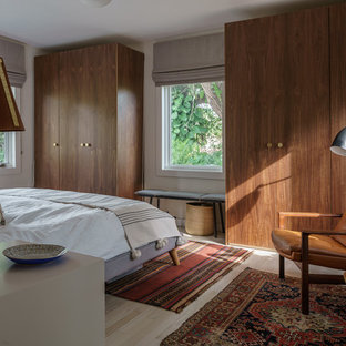 Example of a midcentury modern light wood floor and beige floor bedroom design in Miami with white walls