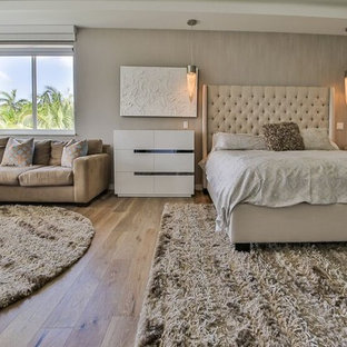 Example of a trendy master light wood floor bedroom design in Miami with beige walls