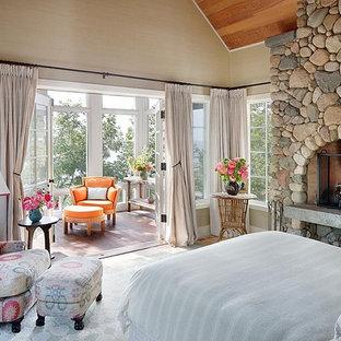 Modelo de dormitorio rústico con marco de chimenea de piedra y chimenea tradicional