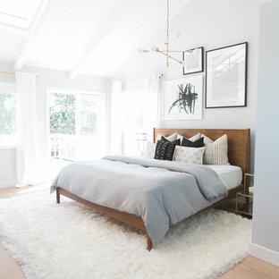 オレンジカウンティの大きいミッドセンチュリースタイルのおしゃれな主寝室 (グレーの壁、淡色無垢フローリング、暖炉なし) のインテリア