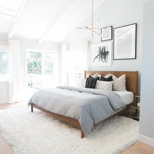 This is an example of a large retro master bedroom in Orange County with grey walls, light hardwood flooring and no fireplace.