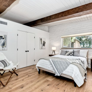 Large retro master bedroom in San Diego with white walls, light hardwood flooring and brown floors.