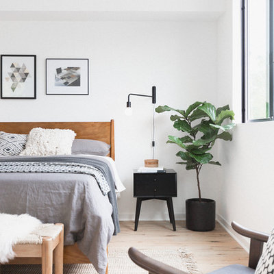 Example of a trendy master light wood floor and beige floor bedroom design in Los Angeles with white walls