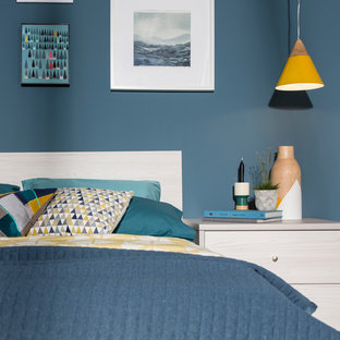 This is an example of a medium sized contemporary guest bedroom in West Midlands with blue walls.
