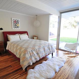 Diseño de dormitorio retro con paredes beige y suelo de bambú