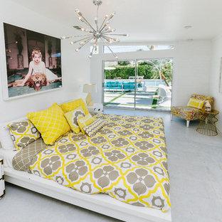 Пример оригинального дизайна: гостевая спальня среднего размера в стиле модернизм с белыми стенами, бетонным полом, стандартным камином, фасадом камина из кирпича и белым полом