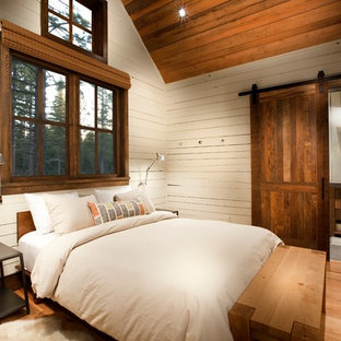 Mountain style guest medium tone wood floor and brown floor bedroom photo with white walls