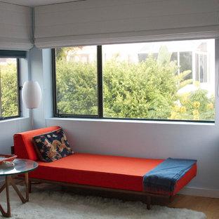Ejemplo de dormitorio principal, retro, de tamaño medio, con paredes azules, suelo de madera en tonos medios, chimenea de esquina y suelo blanco