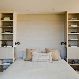 Modelo de dormitorio principal, moderno, grande, con paredes beige y suelo de madera en tonos medios